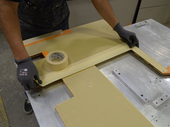 Prepare the base of the seat console assembly for bonding by placing masking tape on the bottom of the base along each edge where parts will be joined.