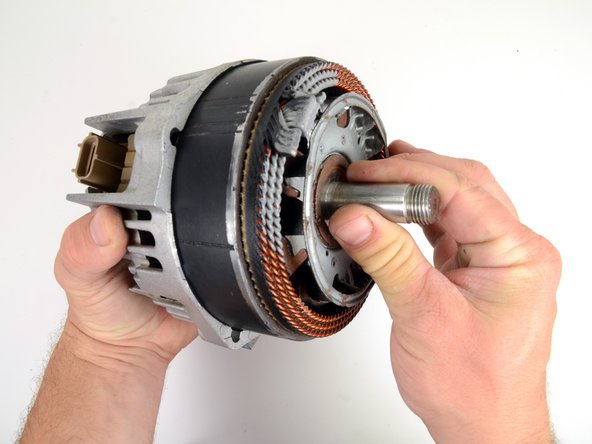 Firmly grasp the main shaft, and slide the rotor assembly into the alternator.