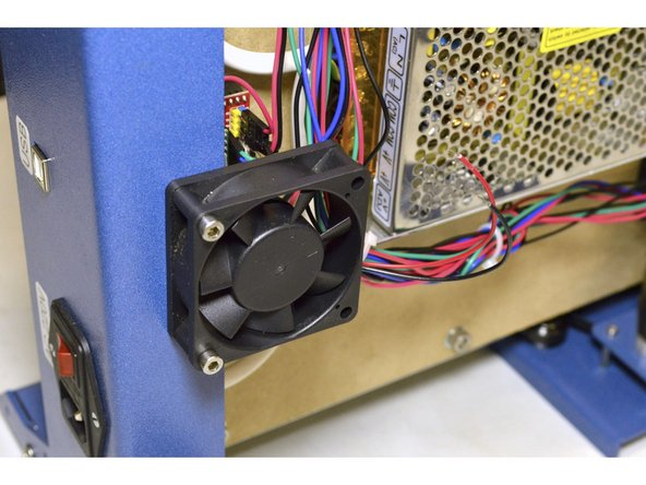 Mount the cooling fan with the sticker facing the electronics and the wires facing the power supplies