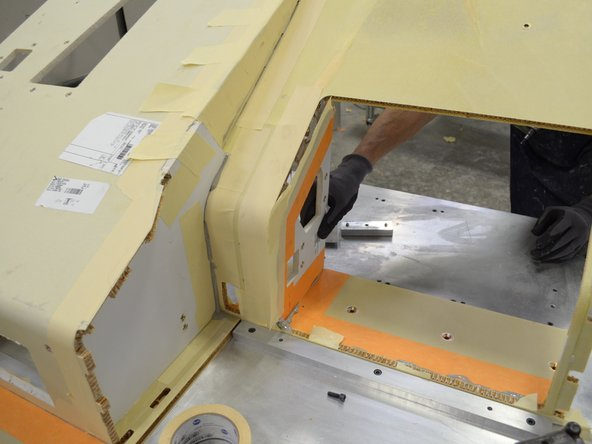 Use a putty knife to score the masking tape covering the mating surface underneath the top piece of the seat console assembly.