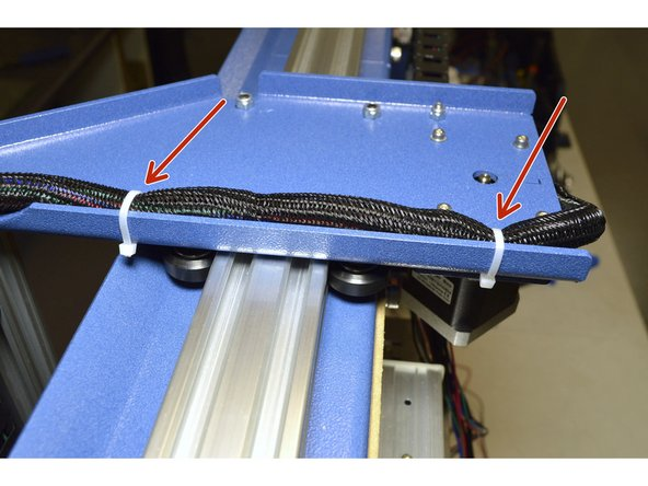 Use the Cable Ties (3 Pcs) and mount the X-Axis Cables to the Left Y-Carriage Plate as shown.  There are slots for all 3 cable ties in the blue plates