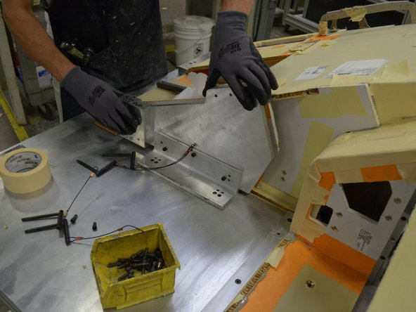 Install the final piece of the seat console assembly and its frame support.