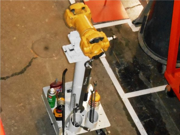 Place drive shaft on rolling fixture and roll under crane. (2 Minutes)
