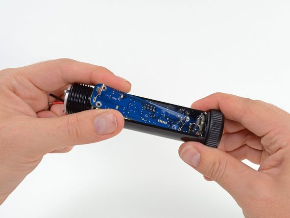 Carefully pull the motherboard towards the front of the Hexbright so that the button on the rear of the motherboard clears the rubber button cover.