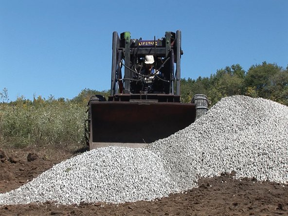 Have XX tons of gravel delivered. Make sure the truck has access to the site and has room to back up and drop the load where you want it.