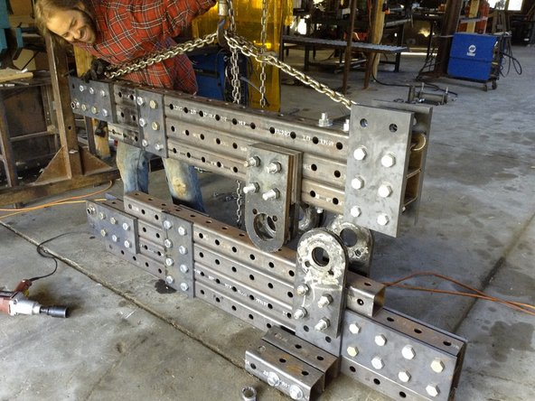 Use the hoist to lift the upper frame into place, making sure the pivot plate holes roughly align.