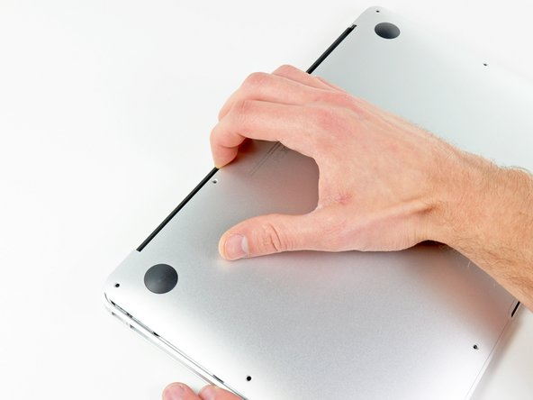 Wedge your fingers between the display and the lower case and pull upward to pop the lower case off the Air.